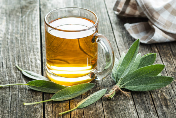 Clear cup of tea beside sage leaves on table
